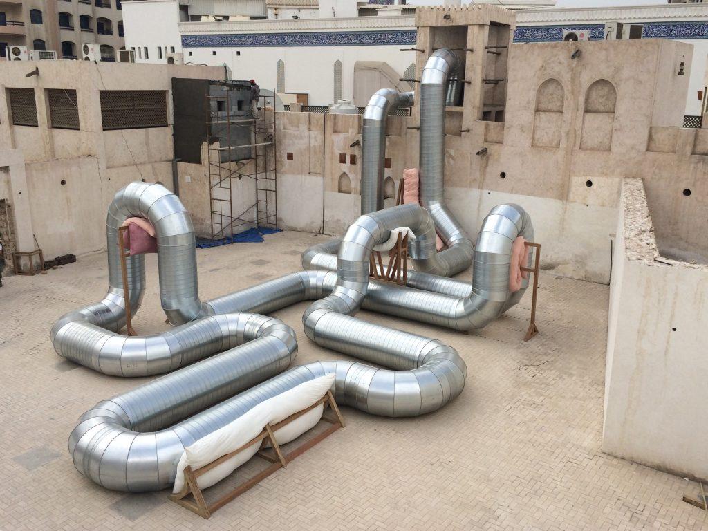 Holly Hendry, Homeostasis (2014) and Homeostasis II, 2018, Galvanised steel ducting, meranti wood, cushions, fan, air. Sharjah Art Foundation + Domaine Vranken Pommery