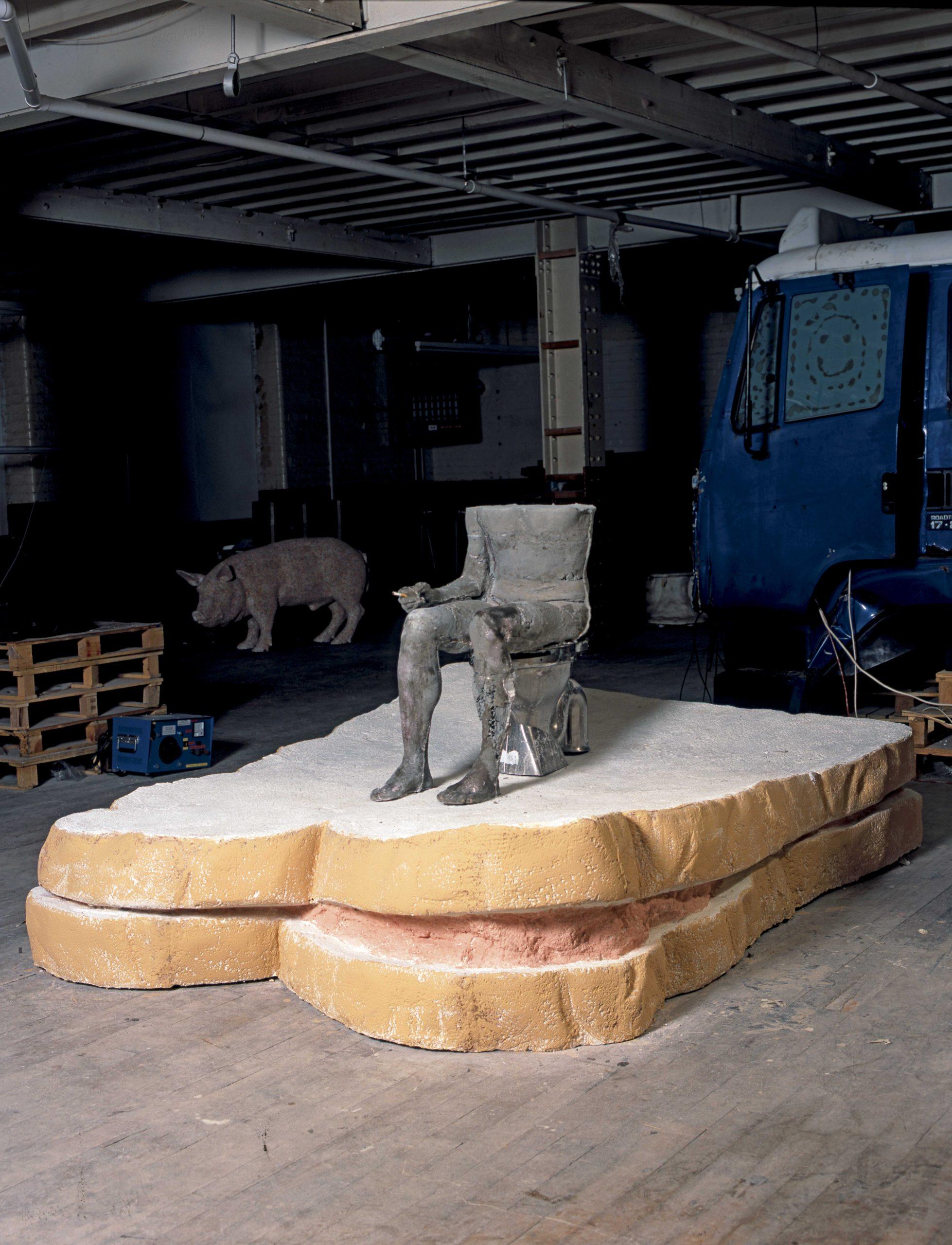 SarahLucas,Cnut,2004 Jesmonite sandwich, concrete figure, cigarette, paint, stainless steel toilet, plastic seat. Sandwich: 60 x 244 x 190 cm figure: 87 x 102 x 43 cm © Sarah Lucas, courtesy Sadie Coles HQ, London