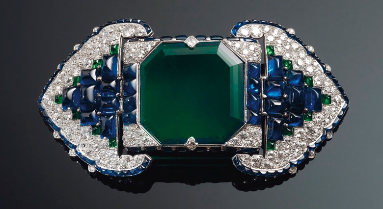 An Art Deco emerald, sapphire and diamond belt buckle-brooch, Cartier. Octagonal step-cut emerald of 38.71 carats, buff-top calibré-cut sapphires and emeralds, old and single-cut diamonds, platinum and 18k white gold (French marks), 3½ in, 1922. Unsigned, partial maker's mark (Atelier Renault), no. 0346, red Cartier case