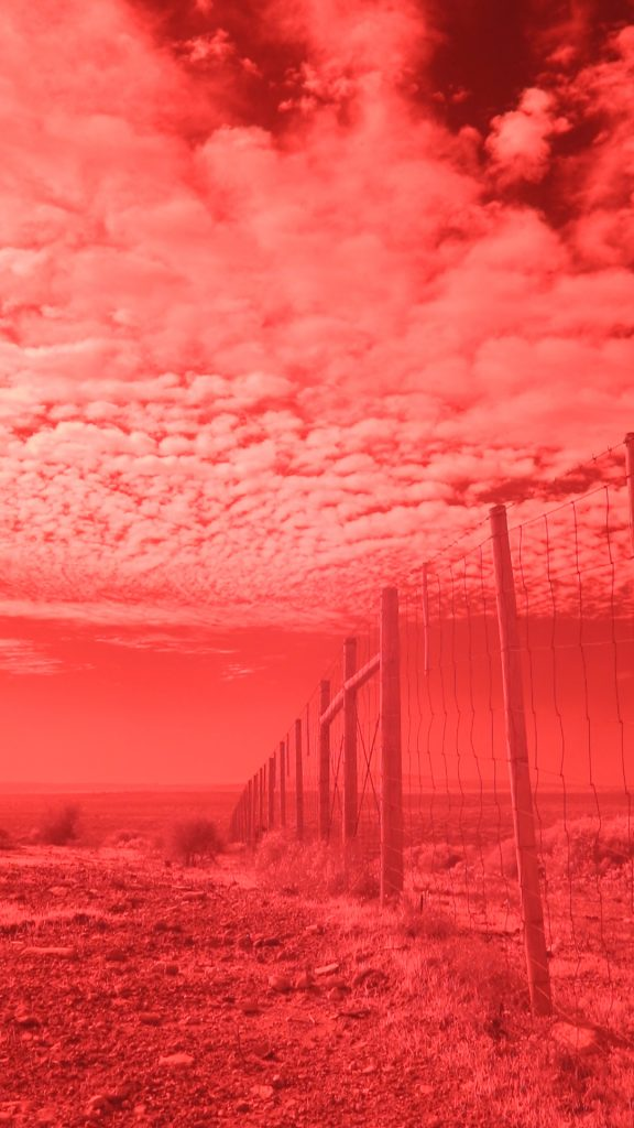 Still from a network located video of a fibre­optic cable landing location in Yzerfontein, South Africa made using a camera adapted to film in the infrared spectrum.?Credit: Detail from Evan Roth, Red Lines (2018). An Artangel commission.