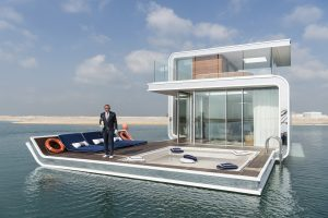 A butler is welcoming the press to a prototype of The Floating Seahorse, an underwater holiday villa, situated at the Heart of Europe, a man-made archipelago 2.5 miles off Dubai. The villa features underwater bedrooms and bathrooms with floor-to-ceiling windows that allow for views of marine life. Each villa comes with a personal butler. By the time the ambitious project is complete there will be more than 125 floating villas, which cost as much as 2,5 million Euro each. Renting the villa will cost 5,000 Euro a day. This photograph is part of the series 'Dubai. Bread and Circuses', a documentary on leisure and tourism in Dubai.