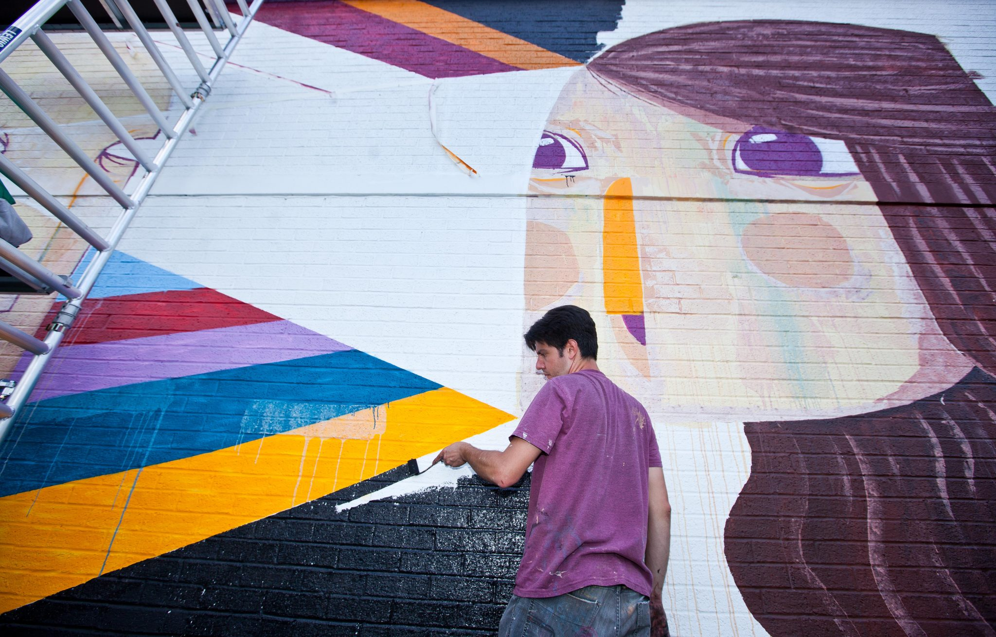 Brazilian Artist and Illustrator Caio Beltran works on his contribution at the UK's first bookable interactive art space in King's Cross, London June 18th, 2017. The giant public canvas is a wall of the Attic self-storage facility on York Way, and via a web app art lovers can vote for a piece to remain or be removed and repainted. Pic by Ben Gurr