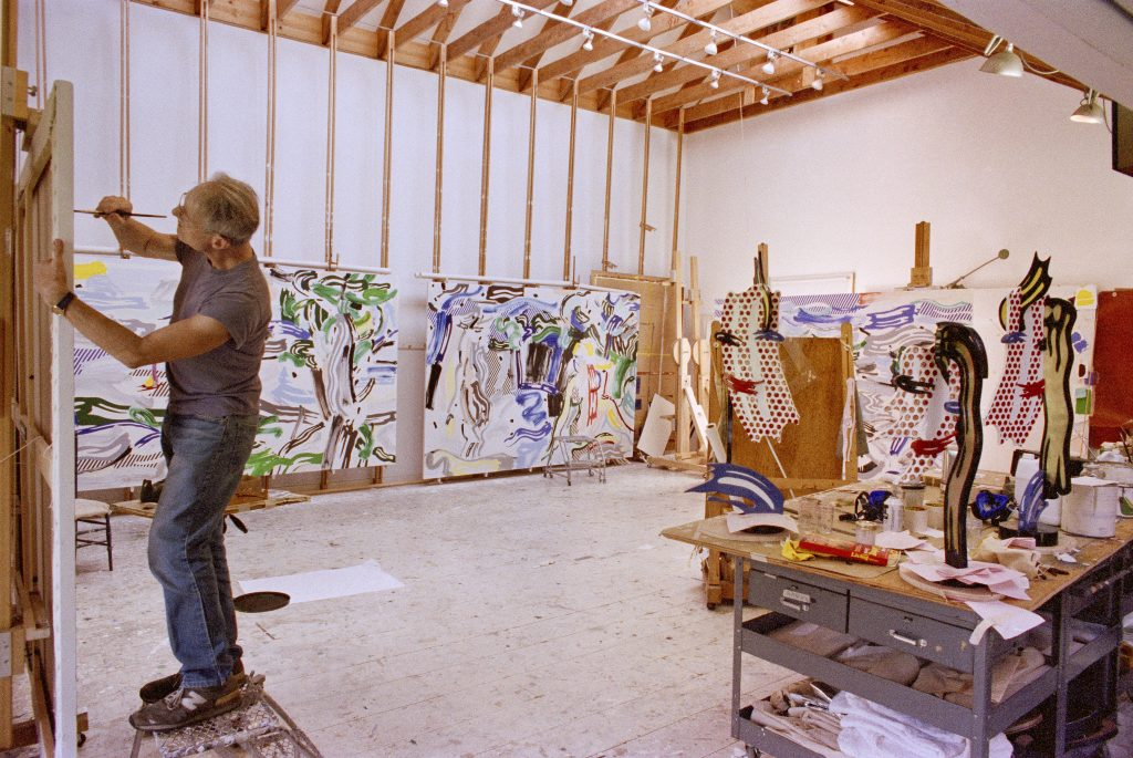Archival image of Roy Lichtenstein working in his Southampton studio with works featured in the exhibition,1987. Photographed by Bob Adelman. Paintings from left to right: River Scene, 1987; Artemis and Acteon, 1987; Left sculpture: Brushstroke Head I, 1987