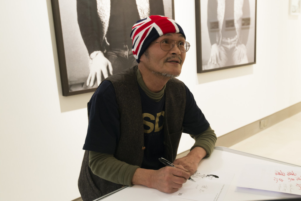 Chu Enoki signing his work at White Rainbow