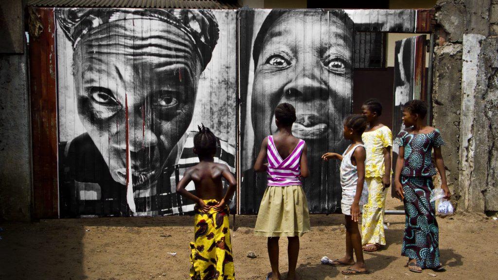 "JR, ""28 Millimètres : Women Are Heroes, Pasting in Monrovia streets, Liberia"", 2008 Colour photograph, polished plexiglas, aluminium, wood 125 x 222 cm ©JR-ART.NET Courtesy Gallerie Perrotin"