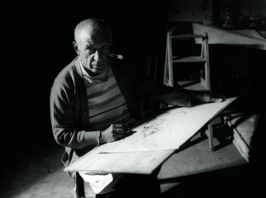 Pablo Picasso drawing in Antibes, summer 1946. Black-and-white photograph Photo © Michel Sima / Bridgeman Images © Succession Picasso/DACS 2019