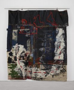 Oscar Murillo, violent amnesia, 2014-2018. Graphite, oil, oil stick, grommets and stainless steel on canvas and linen. 300 x 164 x 15 cm. Courtesy the artist. Photograph: Matthew Hollow