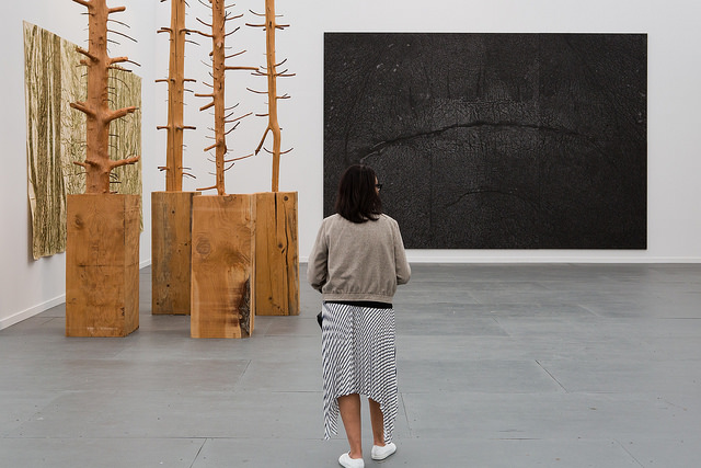 A woman looks at works by Guiseppe Penone at the Marian Goodman Gallery booth at Frieze New York 2015