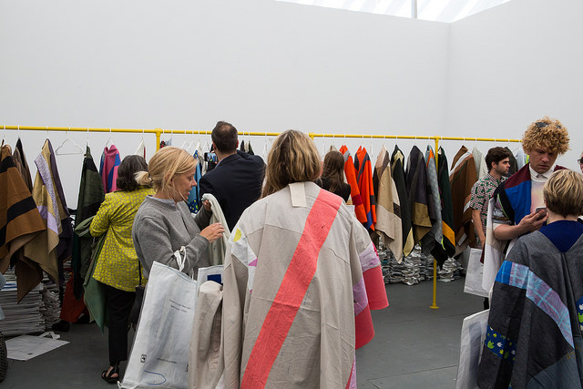 Visitors to Frieze New York 2015 try on wearable art ponchos by Pia Camille