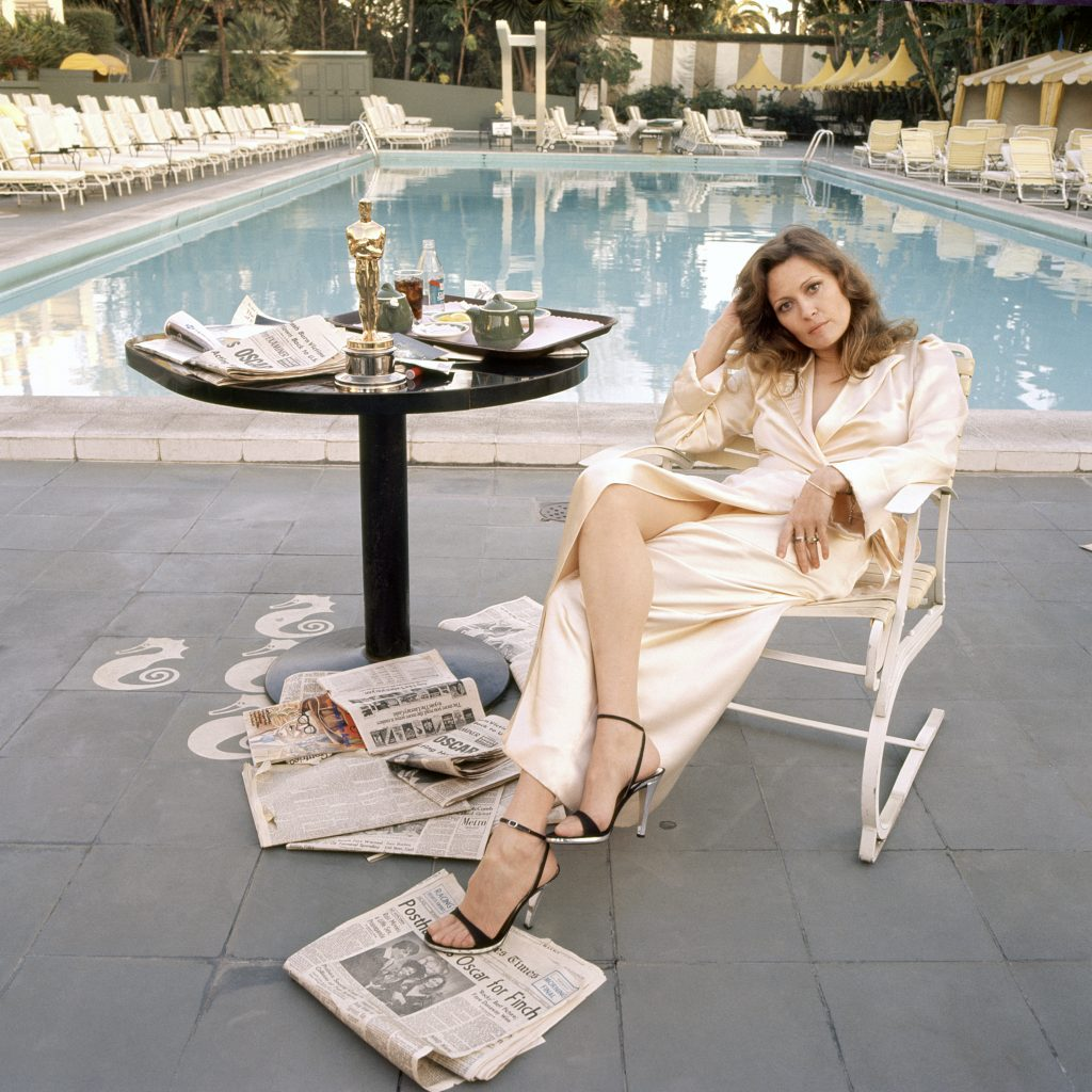 American actress Faye Dunaway takes breakfast by the pool with the day's newspapers at the Beverley Hills Hotel, 29th March 1977. She seems less than elated with her success at the previous night's Academy Awards ceremony, where she won the 1976 Oscar for Best Actress in a Leading Role for 'Network'.