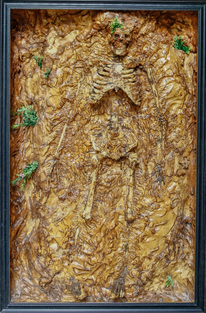 "William York Look at us Now , 2020 Mini physique skeleton set in plaster with fake plants 91 x 61 x 15 cm Sophisticated, intelligent and innovative? What would our ancestors think of the way we treat the Planet today? Earth Eating, or eaten by the Earth. This is quintessentially what happens to every organism on our planet. We get our nutrients from the Earth, we die, decompose and give it back. Its the eternal cycle of life. Eat, breed, die. What happens when the cycle is tainted? As finite beings, we (generally) don't consider our impact to the earth, or the long lasting effects we may bring, both positive or negative. It is our duty to rescue the Earth from us. ""The research reveals that once a tipping point has been passed, breakdowns do not occur gradually like an unravelling thread, but rapidly like a stack of Jenga bricks after a keystone piece has been dislodged."" Jonathan Watts."