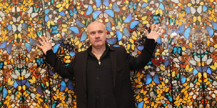 LONDON, ENGLAND - APRIL 02: Artist Damien Hirst poses in front of his artwork entitled 'Doorways to the Kingdom of Heaven' in the Tate Modern art gallery on April 2, 2012 in London, England. The Tate Modern is displaying the first major exhibition of Damien Hirst's artworks in the UK, bringing together the collection over 70 of Hirst's works spanning three decades. The exhibition opens to the general public on April 4, 2012 and runs until September 9, 2012. (Photo by Oli Scarff/Getty Images)