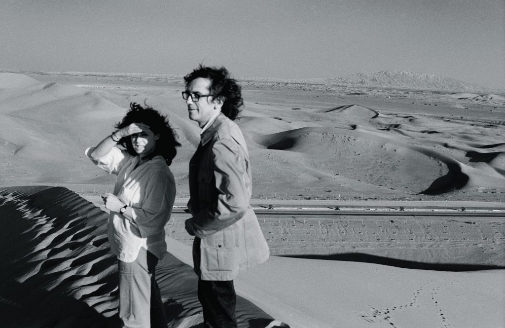 February 1979. Christo and Jeanne-Claude survey the desert from a dune in the UAE desert. Photo- Wolfgang Volz © 1979 Christo