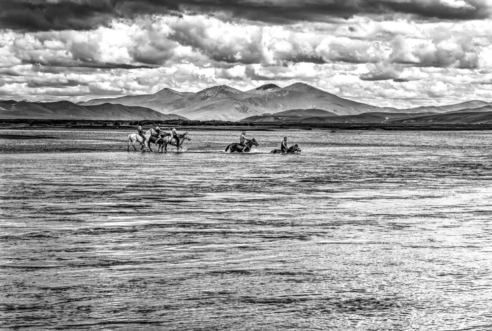 Traversée à la nage de la rivière Dzatchou (Mekong), près du monastère de Guémang, Dzatchoukha, Tibet oriental, Juillet 2016. Chaque été, dans la province de Dzachouka, à 4000m d'altitude au Tibet oriental, sont organisés des jeux et des courses de chevaux. Cette année, un groupe de cavaliers a décidé de traverser le fleuve Dzatchou, qui devient le Mekong lorsqu'il sort du Tibet, à cheval et à la nage. Après avoir pris les photos, je me suis moi-même baigné avec eux. L'eau était bien froide! Swiming with horses accross the Dzachu river (Mekong) with horses. Dzachukha, Eastern Tibet, July 2016.