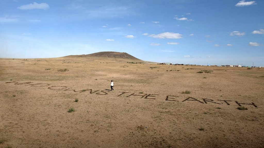 "The Indian artist Vibha Galhotra was invited to make a site specific work for the 2016 Land Art Mongolia (LAM 360°) Biennial. Her work Who Owns the Earth? saw the question placed directly on the ground. The text was made of cow dung, a natural material found in the area. Her work addresses the fragile ecosystem found there, the nomadic culture of the people who live there and the threat due them because of climate change. Galhotra quotes Ban Ki-Moon ""Already, hundreds of millions of people are facing increased hardships. Three quarters of all disasters globally are now climate related…"" Who Owns the Earth? 2016 Istallation mixed media, 3 x 30 meters LAND ART MONGOLIA - 4th Biennial"