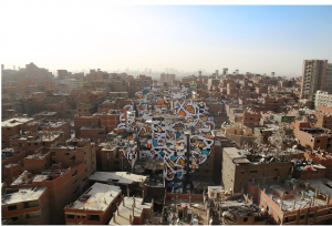 The Tunisian/French artist eL Seed's installation Perception, was painted across 50 buildings in Cairo without the consent of the Government who have stopped street artists making work, and censure artists across many media. The installation was in an area called Manshiyat Nasr, where Coptic Christians live. They are called Zabaleen (the garbage people) but do not use this term themselves. They collect the city's rubbish and recycle it, yet are discriminated against because of their work, and they are seen as dirty. The text eL Seed used is from Saint Athanasius of Alexandria, a 3 rd century Coptic Bishop and states: '?? ???? ??? ?? ???? ??? ?????? ??? ???? ?? ???? ?????' (Anyone who wants to see the sunlight clearly needs to wipe his eye first). The anamorphic image took the artist and a team of workers over three weeks in install, and it could clearly be seen from the nearby Moqattam Mountain. Perception 2016 Installation, paint on 50 buildings